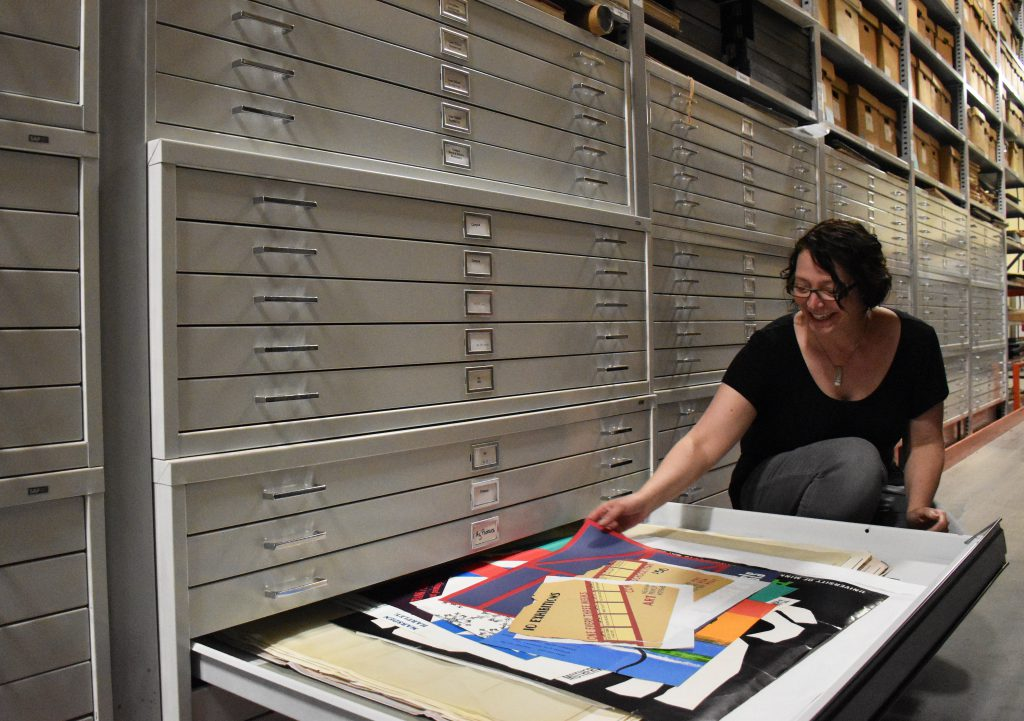 WAM Files Archivist Heather Carroll reaches into a drawer filled with WAM memorabilia.